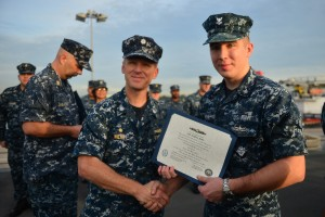 SINGAPORE (July 16, 2013) Electrician's Mate 2nd Class Joshua Roig receives his enlisted surface warfare designation certificate from the USS Freedom (LCS 1) Commanding Officer, Cdr. Timothy Wilke during a pinning ceremony.