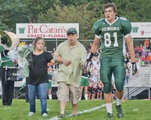 Football star Adam Sandor walks Jacob and Holly across the field during Friday's Westlake High homecoming ceremonies.