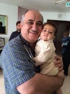 "Dr. Sayed with an infant Syrian refugee. ""We have to do it,"" says Dr. Sayed of the Medical Missions trip made by St. John Medical Center volunteer missionaries."