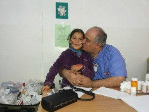 Dr. Sayed and a young patient in a make shift Jordanian medical clinic featuring state-of-the-art love.