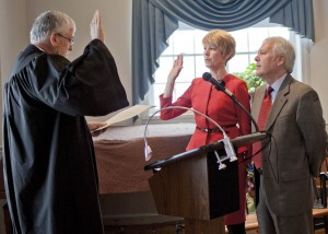 Bay Village Mayor Debbie Sutherland takes the oath of office offered by Judge Robert McClelland with her husband, Bob, at her side.