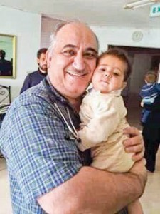 Dr. Sayed hugs a tiny refugee during his medical mission to Jordan.