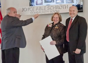 Westlake City Council President Mike Killeen holds up the new Community Room sign named for retiring Director Joyce Able Schroth as Joyce and Mayor Dennis Clough look on.