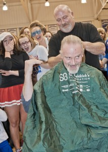 Students get a kick out of barber Jim Sgro of Village Barber Shop as he delivers the final cut to Mr. Schemrich's ponytail.