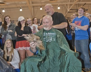 Students share in the fun as Village Barber Jim Sgro buzzes Mr. Schemrich.