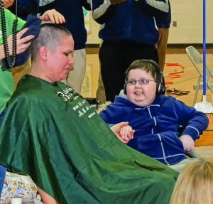 Staff and students at St. Bernadette School in Westlake rallied around 4th grade cancer patient Michael Orbany last Friday for a fund raiser called Brave the Buzz. Over 140 participants had their heads shaved as part of the pledge drive that raised over $50,000. Michael looks on as art teacher Kristen Fox got buzzed.