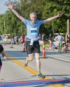 Runner John Cunningham jumps for joy as he crosses the finish line.