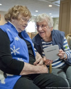 "Edna Villios (left) and Christine Melichar, residents of The Normandy with the Nook they used to read the book ""Rum Run"" by author R.C. Durkee of Grafton, for their book club. ""The Nook is a lot lighter to hold than a book, and you can adjust the type size easily,"" said Christine."