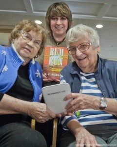 "Normandy Senior Living Community residents Edna Villios (left) and Christine Melichar with the Nook they used to read the book ""Rum Run"" by author R.C. Durkee of Grafton. Both agree that 'going digital' has been fun, and also easy thanks to complimentary classes offered in Nook and iPad use by The Normandy."
