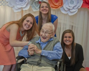 Avon High students Morgan Weiss, Rachel Stark and Maggie Weaver pose with St. Mary of the Woods resident John Kosha for their official Senior Prom photo