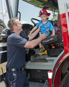 Firefighter Mathias Burke helps a little visitor down from a fire truck cab.