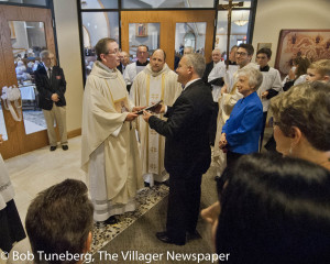 Bishop Lennon receives blueprints and a book of progress of the past 14 months of construction before turning over the keys to the church to St. Raphael Pastor, Fr. Tim Gareau.