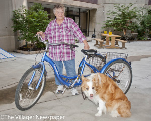 "Pat Piazza with her broken bike and her guide dog, Sun. ""I named him Sun because he is big and round and yellow,"" she says."