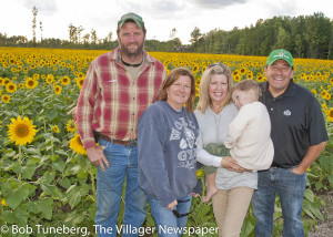 Farmer John Betzel (left) planted 2 million sunfower seeds on 16 acres in Avon to bring the Prayers from Maria field to life again this summer. He had to plant it twice, after June rains washed the first crop away. He is pictured here with his wife, Ruth, and Ed & Megan McNamara.