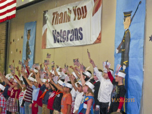 """The First Grade USA Flag wavers during the grand finale of """"God Bless the U.S.A."""" honor Veterans."""