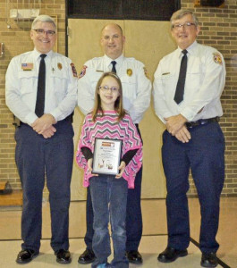 Holly Lane third grader Paige Bammerlin is presented a plaque by Middleburg Heights Assistant Fire Chief John Desmarteau, who is president of the NEOFPA, Westlake Assistant Fire Chief Mike Freeman and Westlake Fire Lit. Greg Mortus.