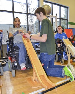 YC Boccia Team members Rashad Switzer and his teen volunteer partner, Zac Alberty, practice while Coach Sean Walker looks on. Boccia is the adapted form of bocce.