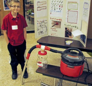 Bassett Elementary School fourth grader T.J. Rintamaki with the vacuum cleaner he modified specifically to pick up Lego blocks. T.J. took the overall second-place award. (Photo Credit: WestLife Newspaper)