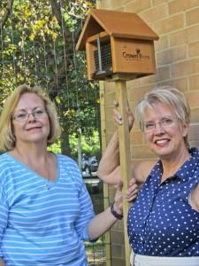 Avon-on-the-Lake Garden Club President Beth Murphy and Vice President Jennifer Fenderbosch with  bee house at Avon Lake Public Library's Children Vegetable Garden.