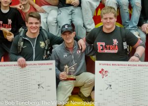 Winning Ways… Elyria High wrestling coach Erik Burnett shares a smile with the Pioneers two champs after the team won the championship at the 56th annual Brecksville Tournament in December. JT Brown (left) won the 182 pound title while Kevin Vough (right) took the 285 pound crown.