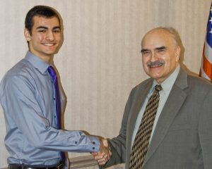 "Alex Stamatis, left, of Avon High School, is congratulated by program producer Jim Mehrling for winning ""Standout Scholar"" honors on the Scholastic Games quiz program on WEOL radio (AM 930)."