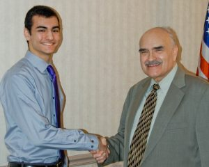 "Alex Stamatis, left, of Avon High School, is congratulated by program producer Jim Mehrling for winning ""Standout Scholar"" honors."