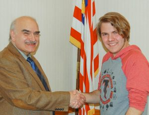 """Michael Durdak, right, of Firelands High School, is congratulated by program producer Jim Mehrling for winning """"Standout Scholar"""" honors."""